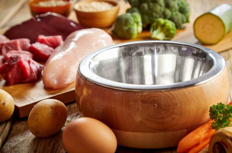 Ciotola vuota del cane del metallo con gli ingredienti alimentari fotografia stock libera da diritti