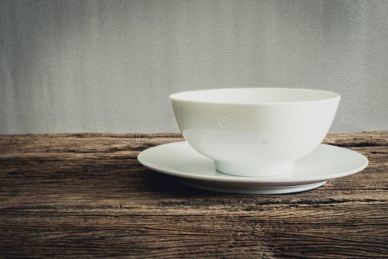 Ciotola vuota e piatto bianco sul ripiano del tavolo di legno immagine stock