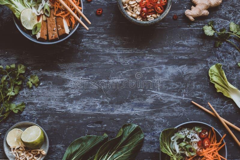 Ciotole asiatiche deliziose con le tagliatelle di riso, le verdure ed il tofu sopra immagini stock libere da diritti