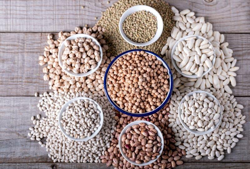 Ciotole bianche con vari legumi veduti da sopra immagine stock libera da diritti