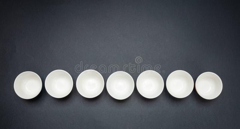 Ciotole ceramiche pulite bianche in una fila, fondo nero, spazio della copia, vista superiore illustrazione vettoriale