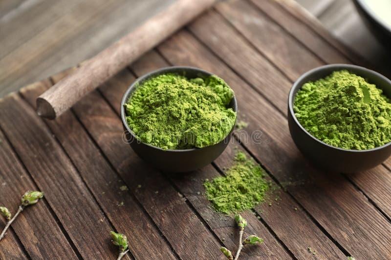 Ciotole con il tè verde in polvere di matcha sul bordo di legno immagine stock libera da diritti