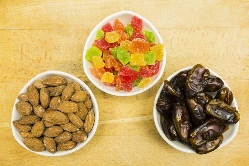 Ciotole con le aggiunte ai dolci ed ai dessert: datteri secchi, ananas candito e mandorle sgusciate Vista da sopra fotografia stock libera da diritti