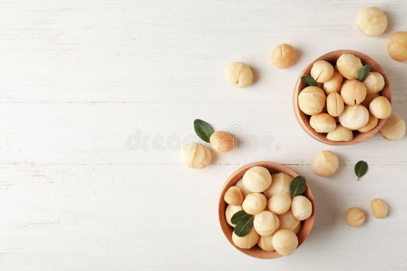 Ciotole con le noci di macadamia organiche sgusciate fotografia stock