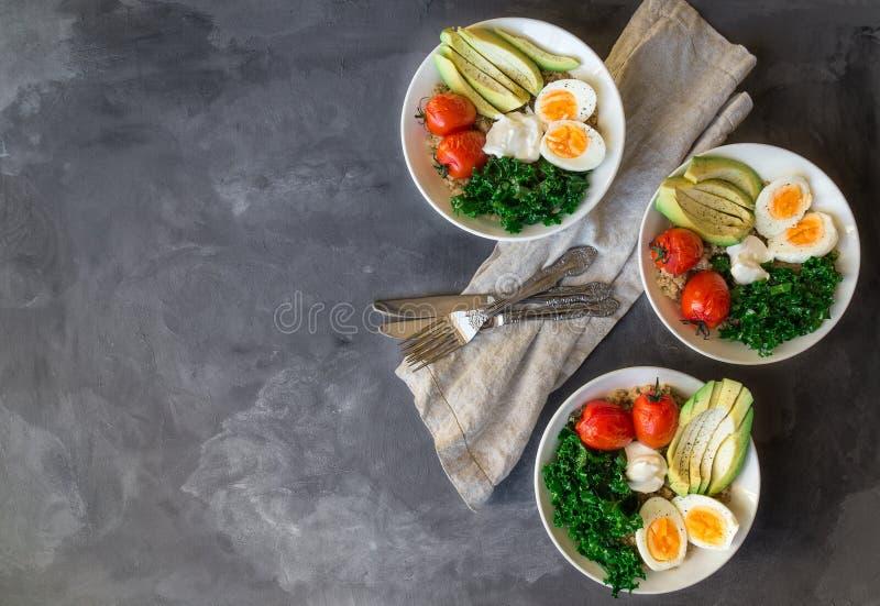Ciotole della quinoa della prima colazione con i pomodori al forno, l'avocado, il cavolo, gli uova sode ed il yogurt greco fotografia stock libera da diritti