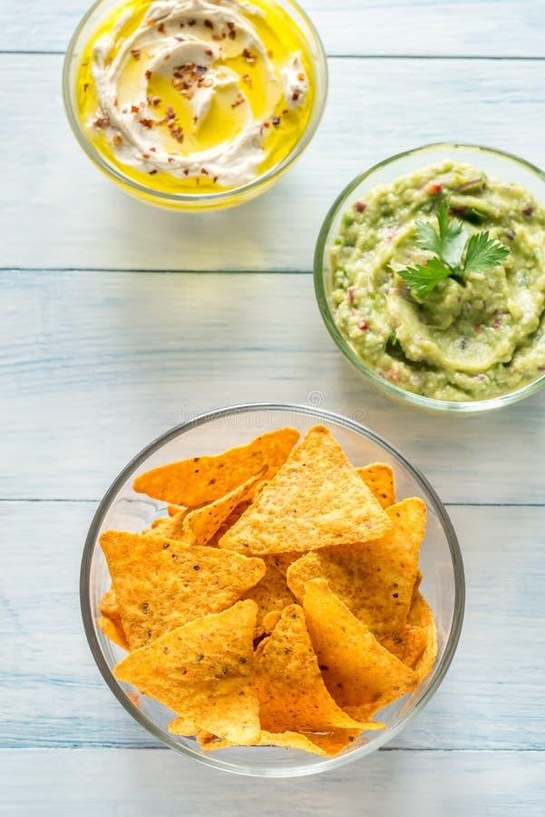 Ciotole di hummus e di guacamole con i chip di tortiglia immagini stock
