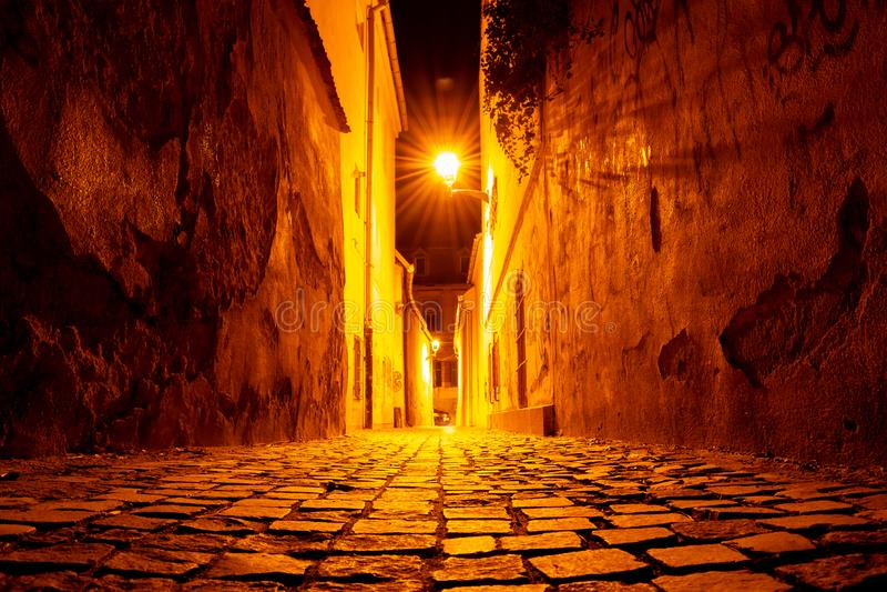 Ciottoli alla notte su una via medievale stretta con le pareti incrinate e avvizzite, accese nella città arancio Sibiu luminosa d immagini stock libere da diritti