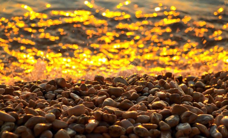 Ciottoli e mare al tramonto fotografie stock libere da diritti