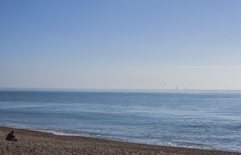 Ciottoli orientali di Eastbourne, Sussex sulla spiaggia e sui cieli blu; giorno soleggiato immagine stock