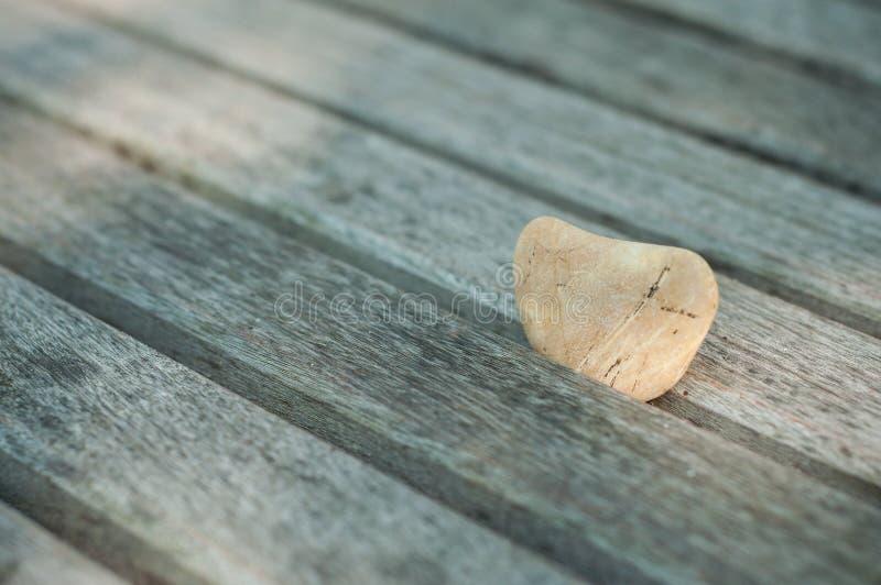ciottolo di pietra nel cuore a forma di sul banco di legno in all'aperto - concetto di amore fotografia stock libera da diritti