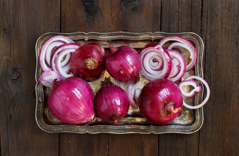 Cipolle rosse su una tavola di legno immagini stock libere da diritti