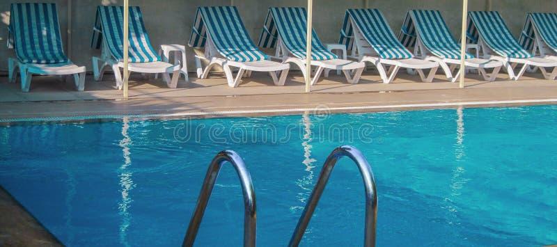 Cirali,土耳其,2014年9月有清楚的大海,镶边蓝色和白色日光甲板的–热带游泳场主持休息室 库存图片