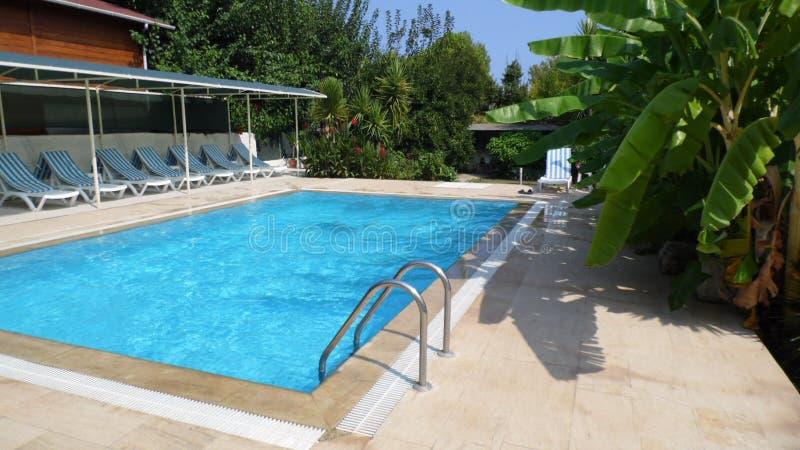Cirali, la Turquie, piscine tropicale septembre 2014 d'†«avec l'eau bleue claire, le salon bleu et blanc rayé de chaises de so photographie stock libre de droits