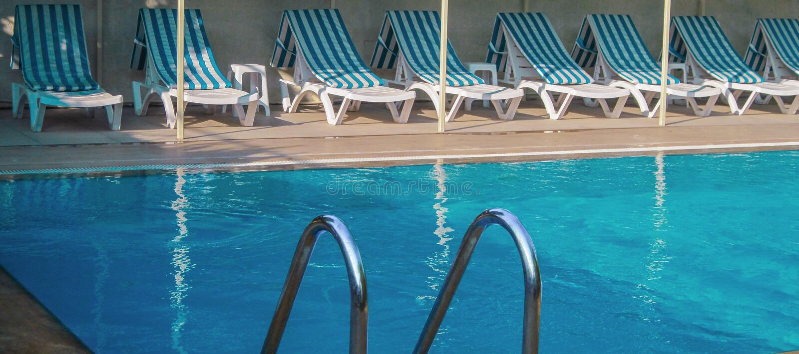 Cirali, Turkey, September, 2014 – Tropical swimming pool with clear blue water, striped blue and white sun deck chairs lounge stock image