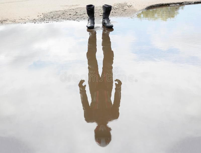 Circa l'acqua valga le scarpe di moto Nella riflessione del motociclista in marcia immagine stock