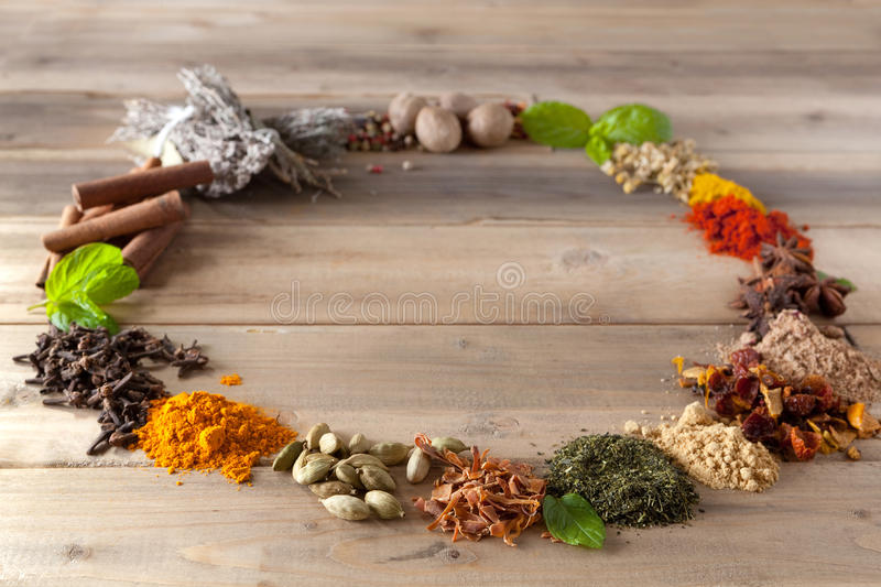 Circle border of spices and herbs. Colorful circle of spices and herbs on a wooden table royalty free stock photography