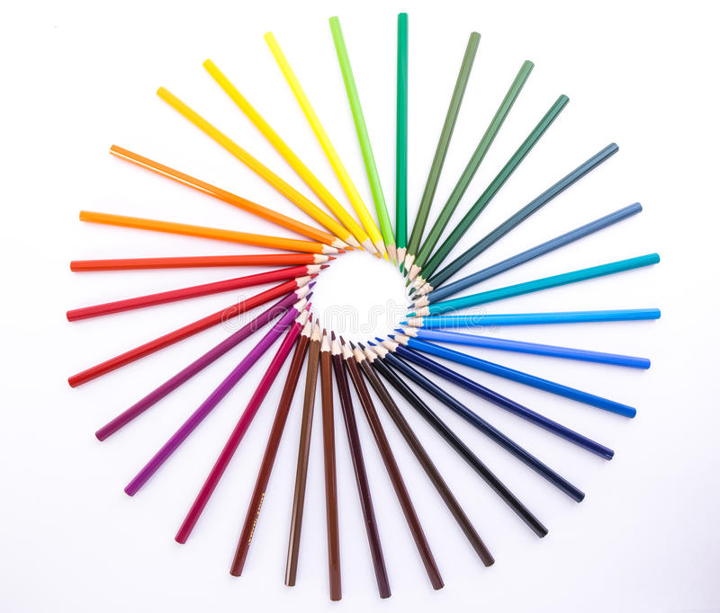 Circle of colored pencils on white background stock image