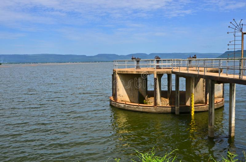 Circle concrete overflow in the water of reservoir. And beautiful scenery in Thailand stock photography