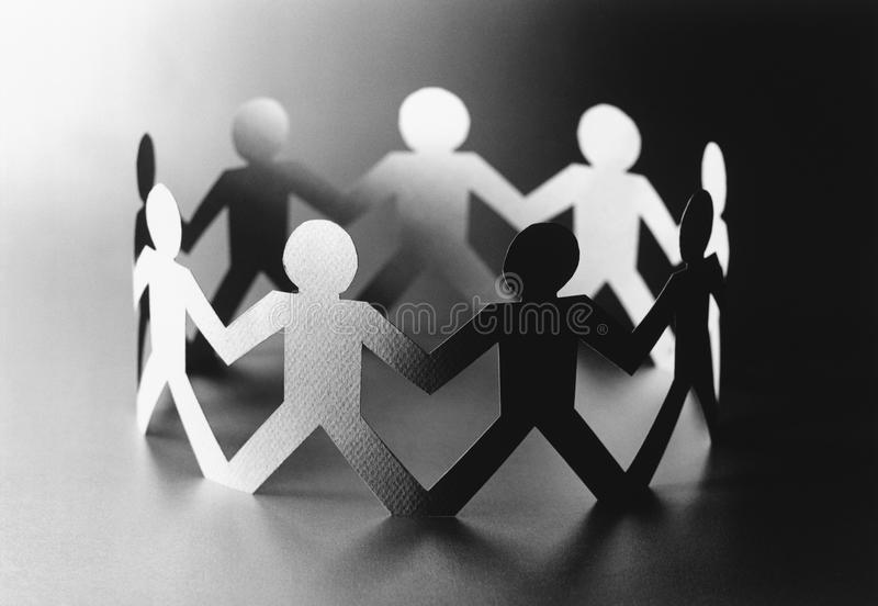 Circle of cut out paper figures (b&w) stock photography