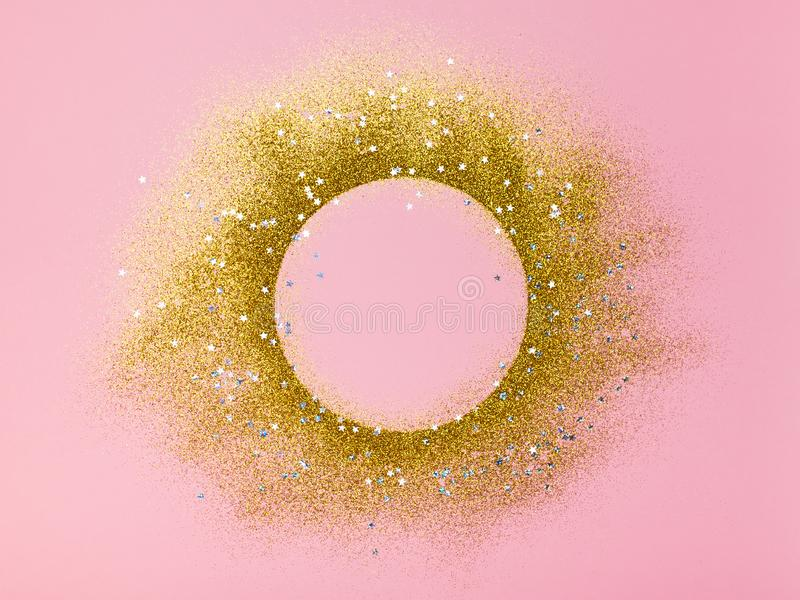 Circle frame of golden glitter, shimmer on pink background stock images