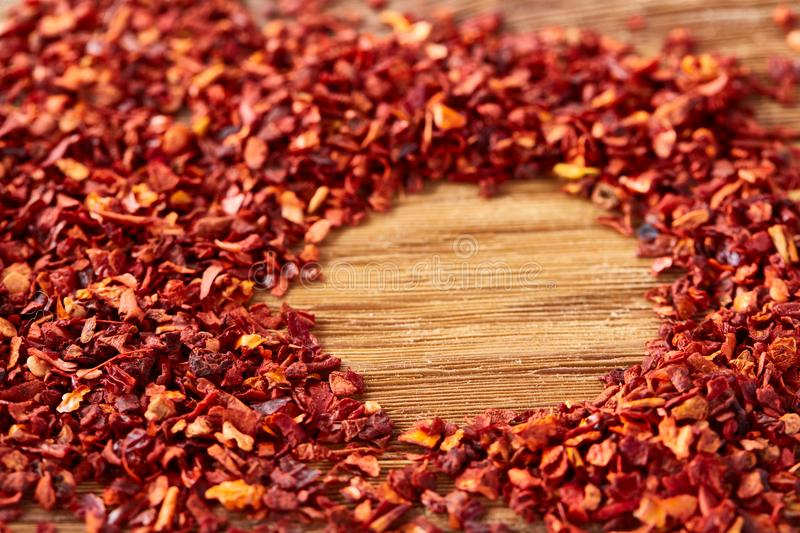 Circle framing made of dried chilly flakes on rustic wooden background, top view, close-up, macro, selective focus. royalty free stock images