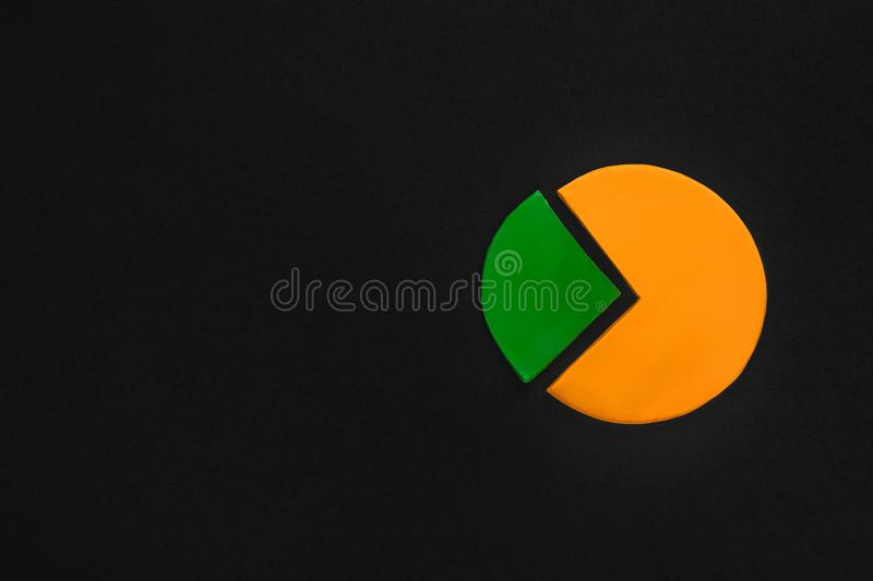 A circle graph made from plasticine on black background on black background, shot from above, aligned to the right royalty free stock photo