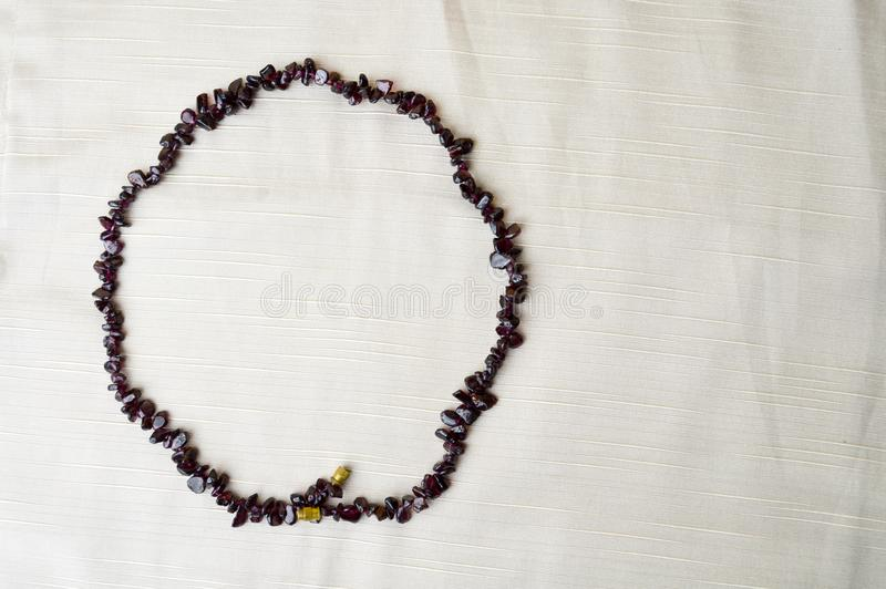 The circle is made of female beautiful beads, necklaces of brown dark stones, amber with a background of beige fabric stock image