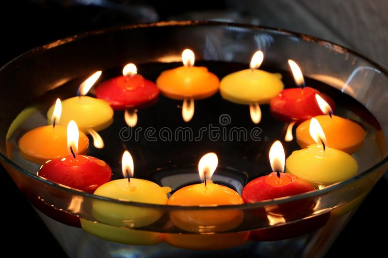 Circle of many candles in colors: yellow and orange red. Floating above water. In a bowl. celebration. A circle of lots of burning candles in colors: yellow and royalty free stock images
