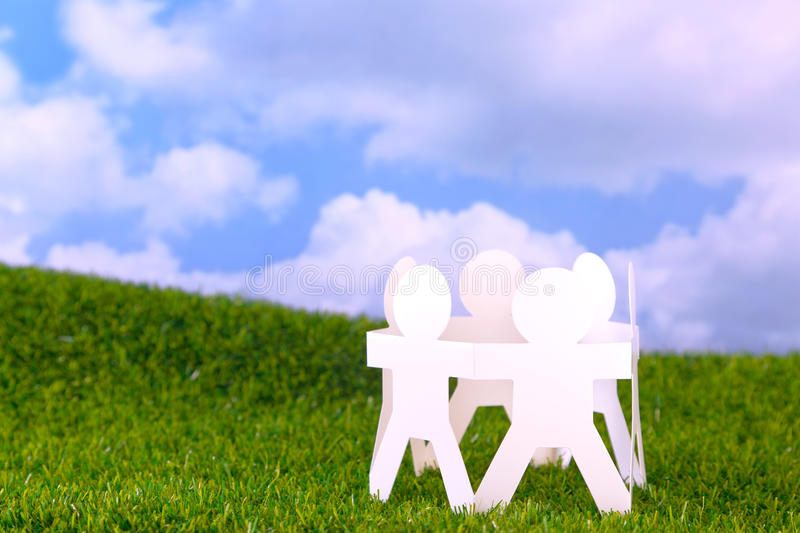 Circle of paper men. Concept image circle of paper men holding hands in a field with sky background stock image