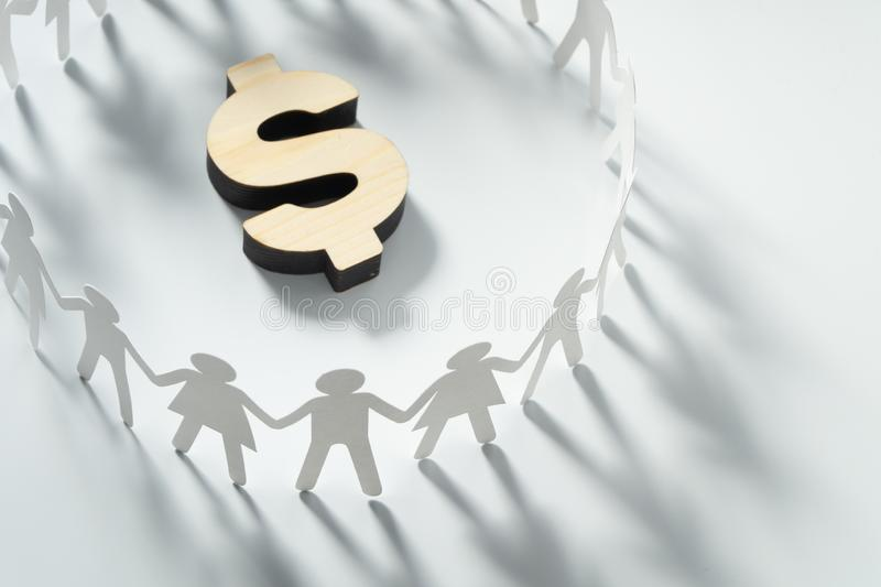 Circle of paper people holding hands in front of big dollar sign. Consumerism, economy concept. Group of paper people holding hands in front of big dollar sign royalty free stock photography