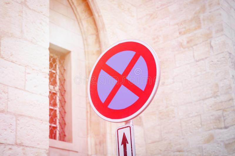 Circle traffic sign with a red cross on a blue background. No stopping or parking. Prohibiting traffic sign. Toned photo stock image