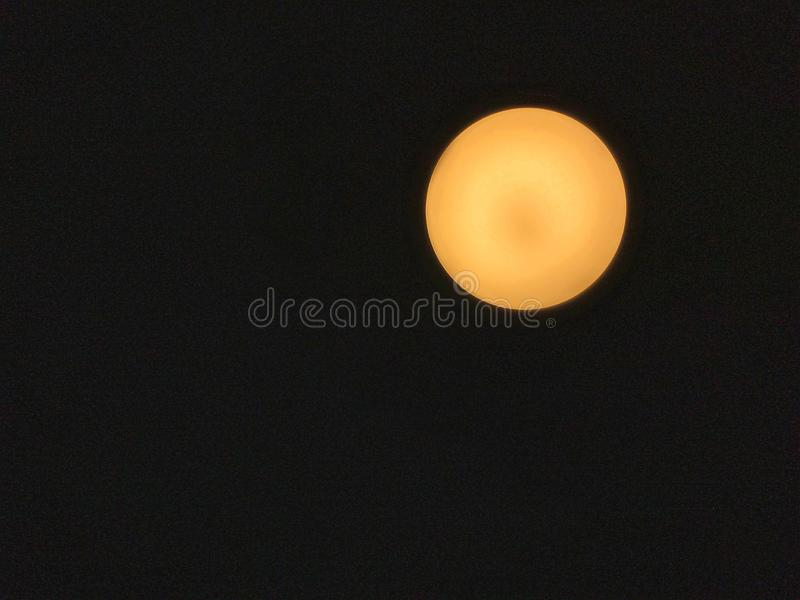 Circle warm white lighting lamp panel on ceiling by bottom view with soft focus. stock photography