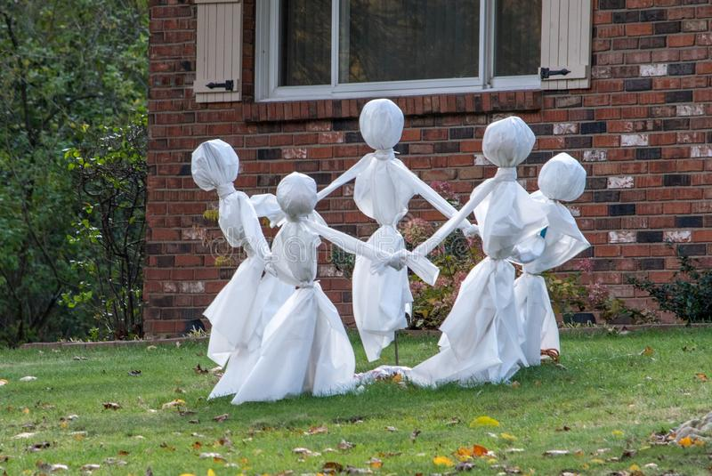 A circle of white clad ghosts play a game royalty free stock photos