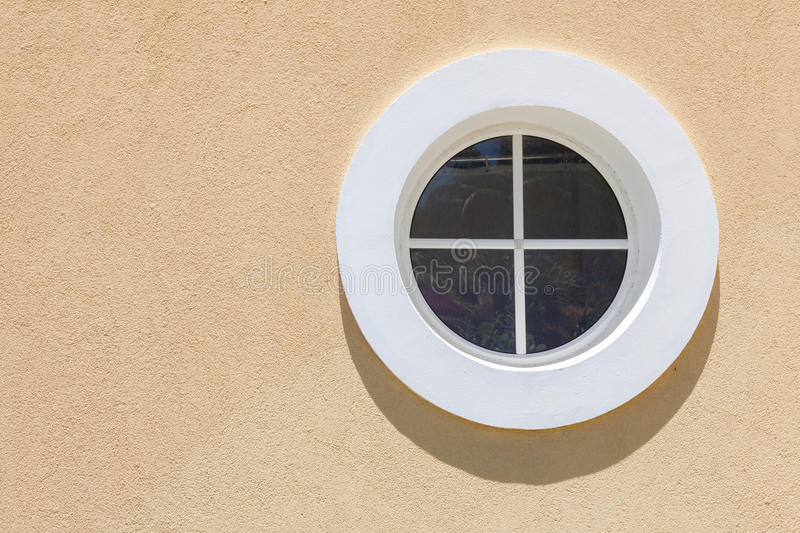 Circle white window with small shadow on the texture wall. stock photo