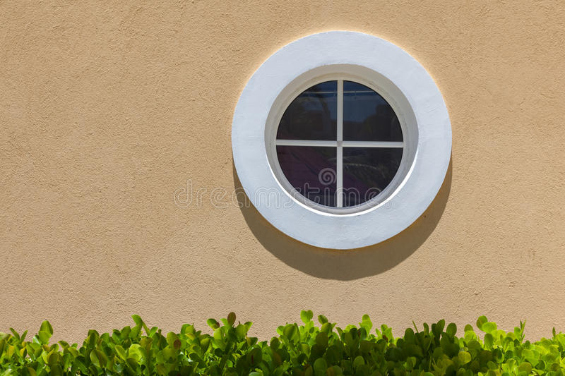 Circle white window on the texture wall. Small shadow and green leaves. royalty free stock photography