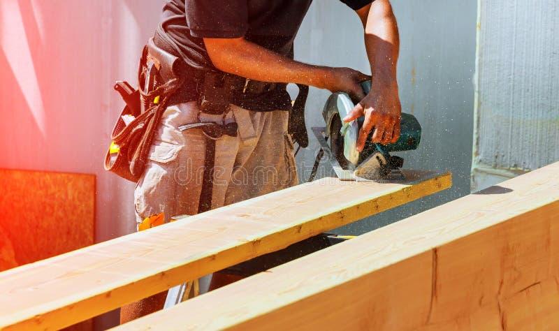 Circolare ha veduto Carpentiere Using Circular Saw per il fascio di legno fotografia stock