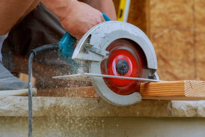 Circolare ha veduto Carpentiere Using Circular Saw per il fascio di legno immagini stock