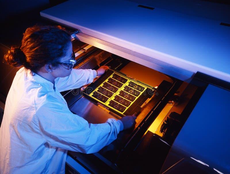 Circuit board technician. Technician removing circuit boards from a testing machine