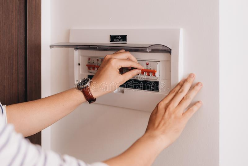 Circuit breaker board displays many switches. A finger is about to turn it back on.  stock photo