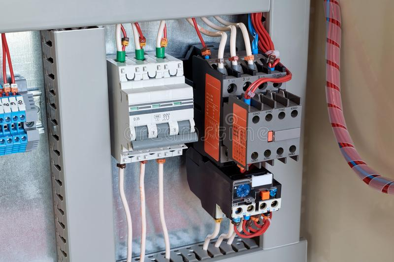 Circuit breaker, contactor or starter with additional contacts and thermal relay in electrical Cabinet. Electric control Cabinet for pumps or motors. The wires stock images