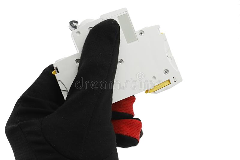 Circuit breaker module for domestic electric installation held in left hand in black and red coloured glove, white background. Circuit breaker module for royalty free stock photography