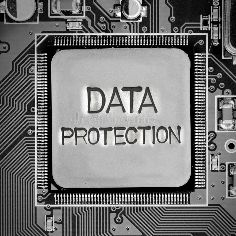 Circuitboard and Chip Concept. Macro photo of circuit board and chip with DATA PROTECTION words imprinted on metal surface royalty free stock images