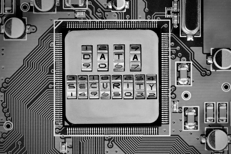 Circuitboard and Chip Concept. Macro photo of circuitboard and chip with DATA SECURITY words imprinted on metal surface stock image