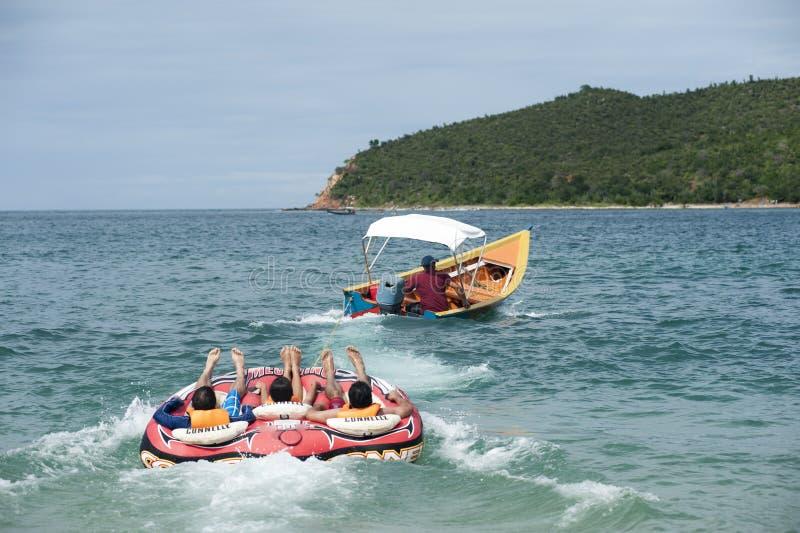 Circulaire gonflable étant remorquée derrière un bateau avec des personnes ayant l'amusement photo stock