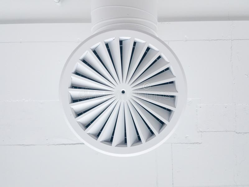 Circular Air Conditioning Grille on White Colored Ceiling. A closeup view of a commercial air conditioning grille painted in white stock photos