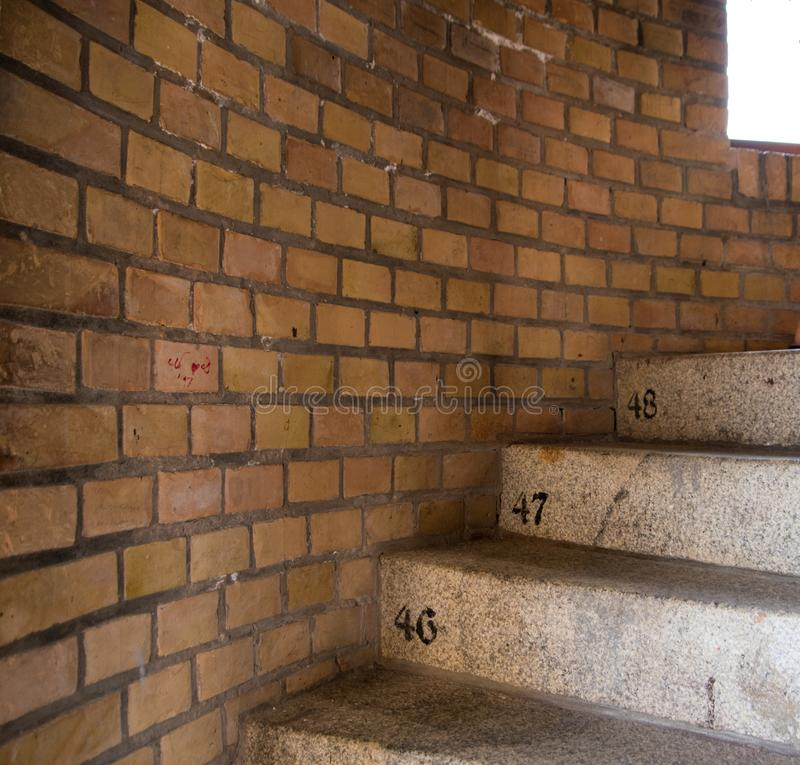 Circular concrete staircase with beige brick background. Stairs royalty free stock images