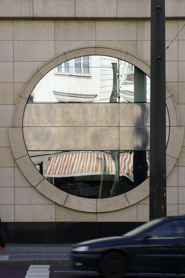 Circular decoration mirror. A circular decoration mirror on the exterior facade of a building with passing traffic stock photography