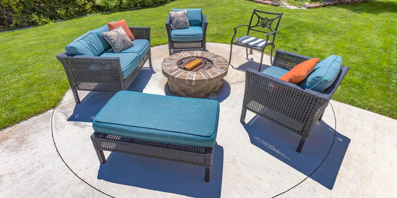 Circular fire pit and chairs on a sunny backyard. A circular stone fire pit surrounded by chairs with blue cushions and pillows. The fire pit is on a backyard royalty free stock photography