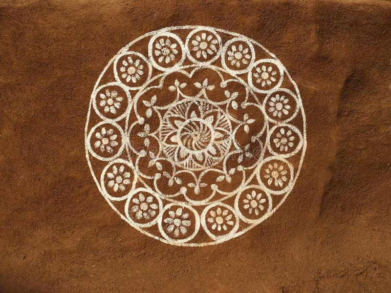 An Indian tribal art and drawing. A circular floral design or Madala painted on mud wall covered with cow dung royalty free stock photo