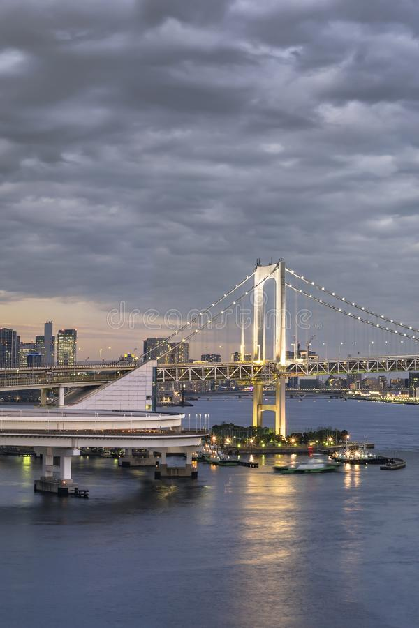 Circular highway leading to the Rainbow Bridge with Cargo and cruise ships moored or sailing in Odaiba Bay of Tokyo.  royalty free stock photos